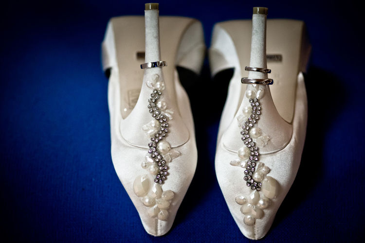 Jewelry Fashion Blue Close-up Colored Background No People Two Objects White Color Art And Craft Elégance Pair Still Life Luxury Wealth Blue Background Personal Accessory Wedding Shoes Wedding Wedding Rings Embroidery Shoes Heels White Shoes High Heels Embroidered