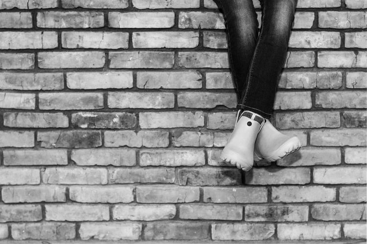 Crossed legs of a young girl in jeans and galoshes sitting on a brick wall
