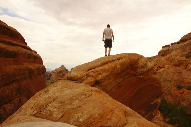 Rear view of man standing on rock formation against sky