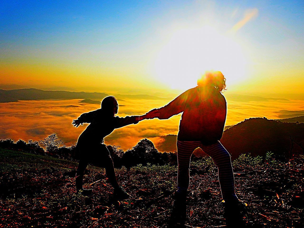 sunset, sky, real people, leisure activity, two people, lifestyles, men, togetherness, standing, land, beauty in nature, silhouette, nature, orange color, full length, field, sunlight, people, friendship, child, outdoors, lens flare, human arm