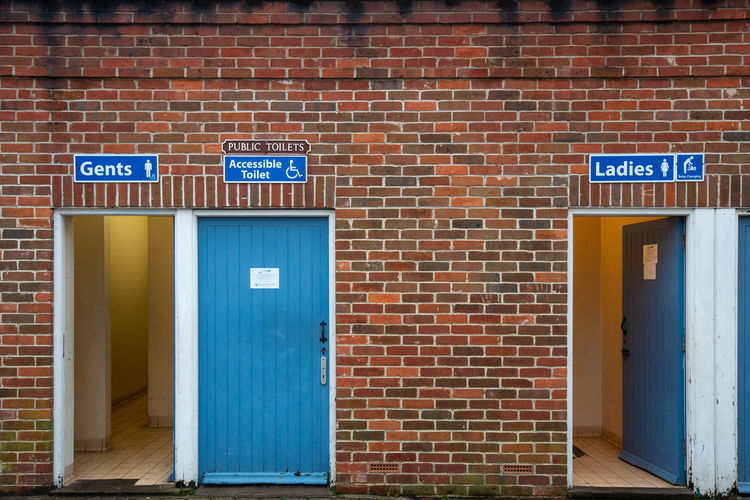 Public Toilets, Ladies, Gents and Accessible toilets with blue wooden doors in an old red brick building. Doors Public Toilet Toilet Absence Architecture Blue Brick Brick Wall Building Building Exterior Built Structure Communication Day Direction Door Doorway Entrance Guidance No People Sign Text Wall Wall - Building Feature Western Script