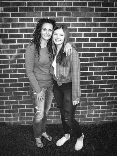 Portrait of smiling mother with daughter standing against brick wall