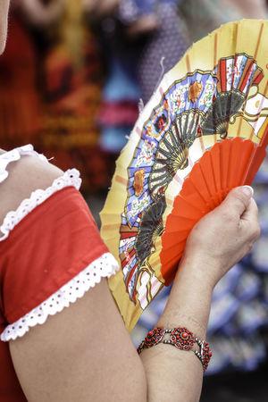 Spanish woman dressed in flamenco, with traditional fan. Seville Fair. Close up. Selective focus. Andalusia Beautiful Dance Dress Flamenco Music Rhythm SPAIN Seville Spanish Traditional Culture Traditional Clothing Woman Clap Clapping Culture Dancers Fan Feria De Abril Festival Folklore Passion Traditional Traditional Festival Women