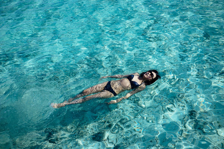 High angle view of woman swimming in a crystal clean ocean