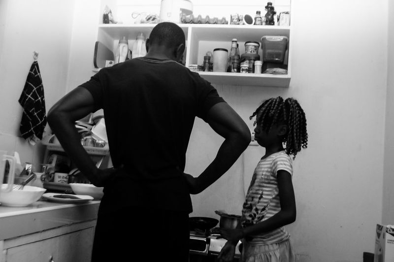 Father With Daughter Standing In Kitchen At Home