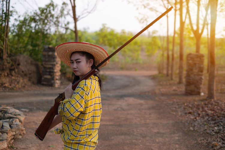Portrait the farmer asea woman wearing a hat hand holding muzzle-loading vintage gun in the farm