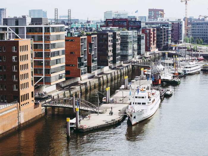 High angle view of boats moored at harbor by buildings in city against sky