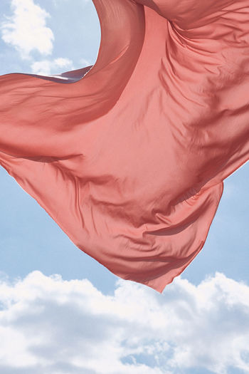 Low angle view of red flag against sky