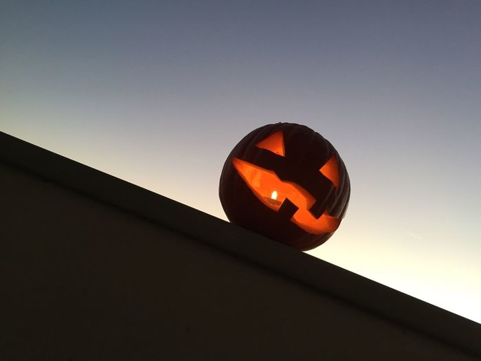 Low angle view of jack-o-lantern on retaining wall against clear sky at dusk