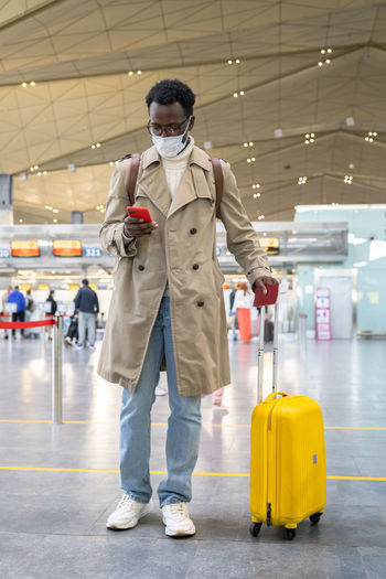 Black traveler man with wear face mask during covid-19 pandemic standing at airport terminal.
