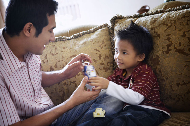 Father And Son Sitting On Sofa At Home