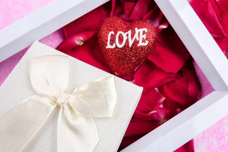 Close-up of gift box with heart shape and rose petals