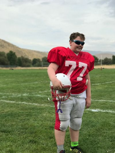 Boy wearing american football uniform on playing field