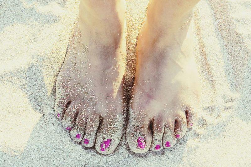 Low section of woman with pink nail polish standing on sandy beach