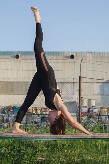 Woman Doing Yoga On Bench Against Sky