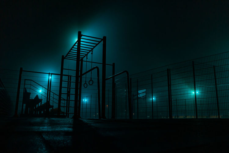 Low angle view of illuminated lights by fence against sky at night