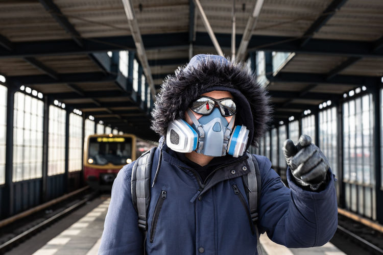 Portrait of young man standing at railroad station with mask on