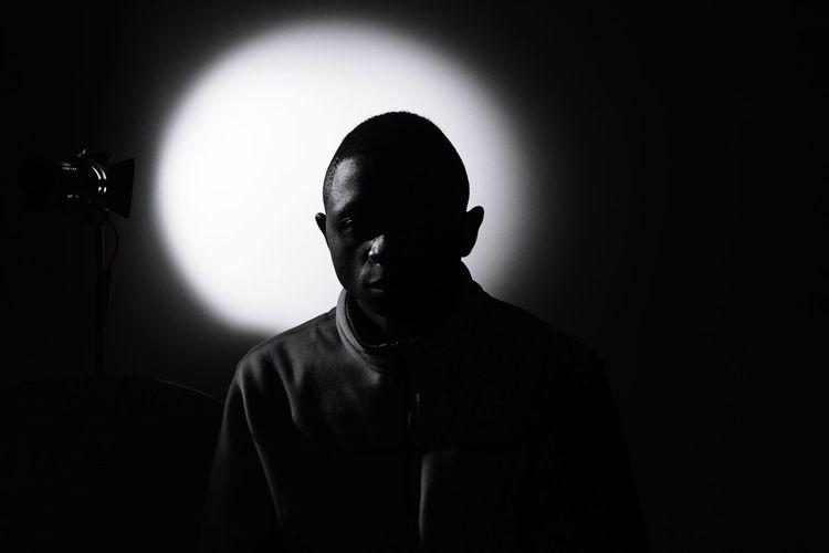 Thoughtful man sitting in darkroom