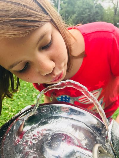 Close-Up Of Girl Looking Into Water