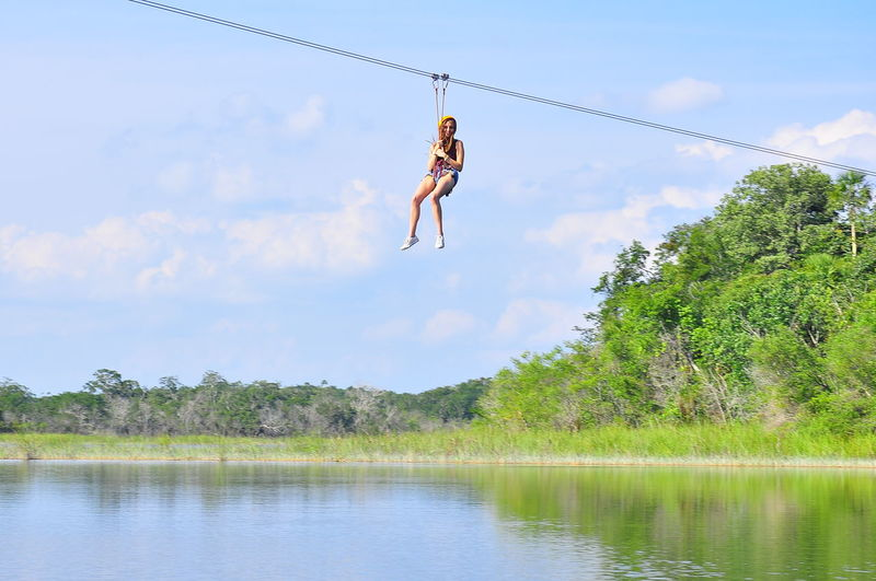 Low Angle View Of Woman Hanging From Zip Line Over Lake Against Sky