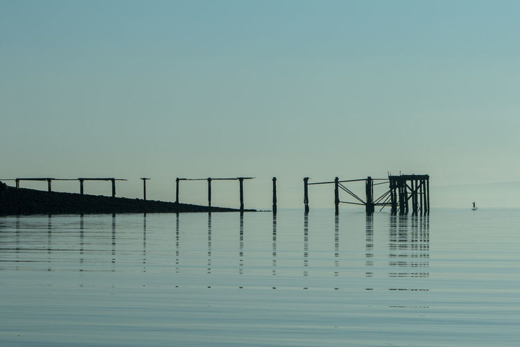 Reflection of pier in sea against clear sky