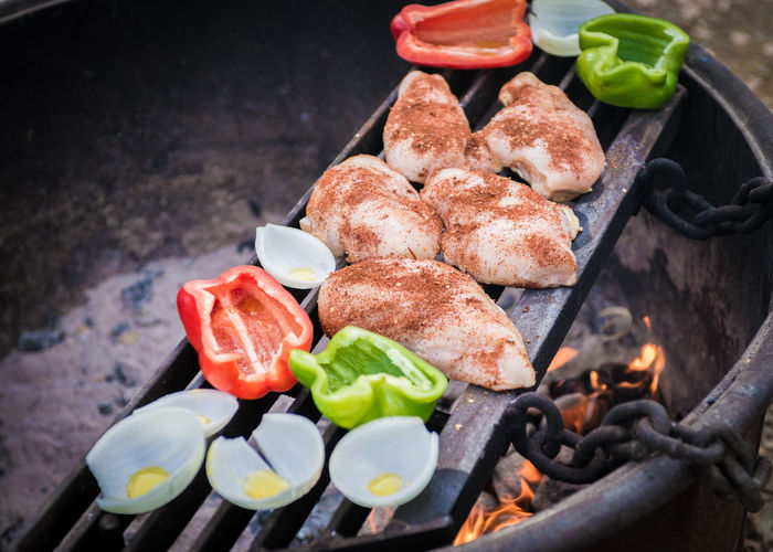 High angle view of meat with vegetables on barbecue grill