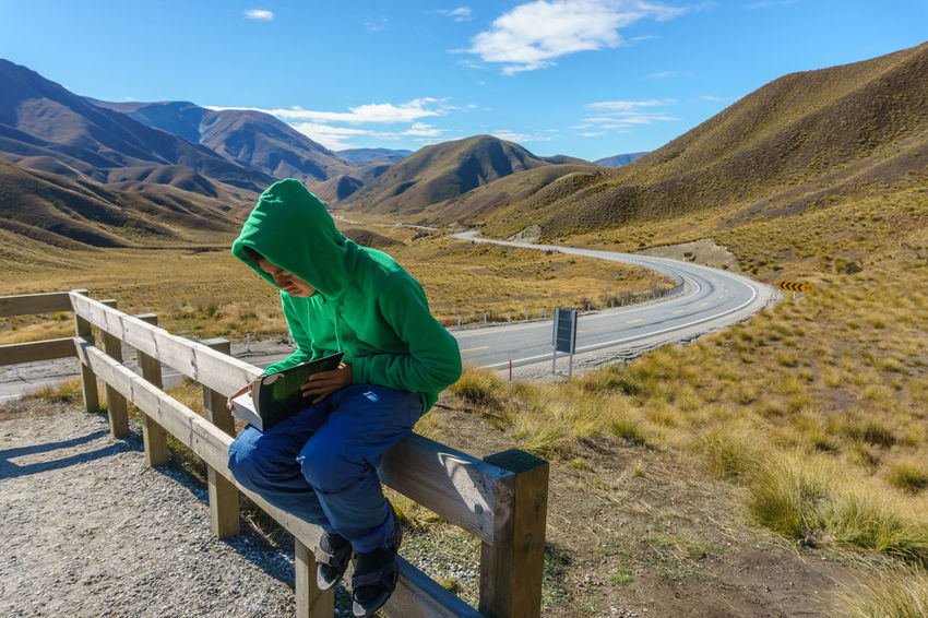 Teenager sitting on fence reading book with road and mountain in background. New Zealand Adult Adults Only Adventure Beauty In Nature Blue Day Gloomy Knowledge Knowledge Is Power Landscape Mountain Nature One Person Outdoors People Reading Out Sitting Sitting In The Car Sky Sport Streetphotography Study Hard Teenager