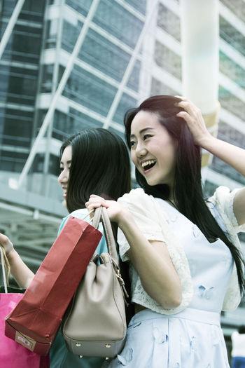 Smiling Friends Enjoying Shopping In City