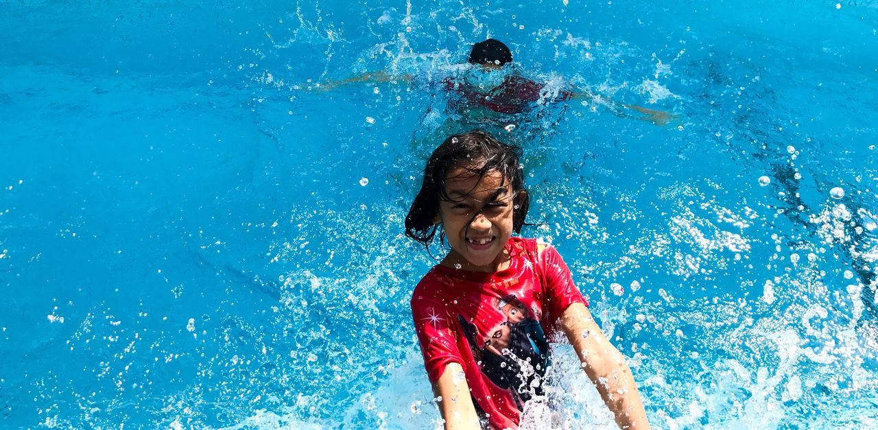 water, childhood, fun, swimming pool, happiness, motion, splashing, enjoyment, red, one person, joy, blue, swimming, smiling, leisure activity, water park, playing, outdoors, day, boys, lifestyles, water slide, cheerful, child, children only, people
