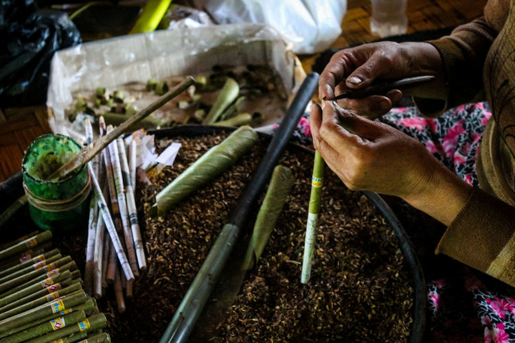 Cropped Image Of Hands Making Cigars