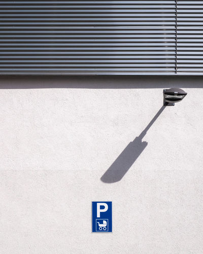 Parking sign on wall during sunny day