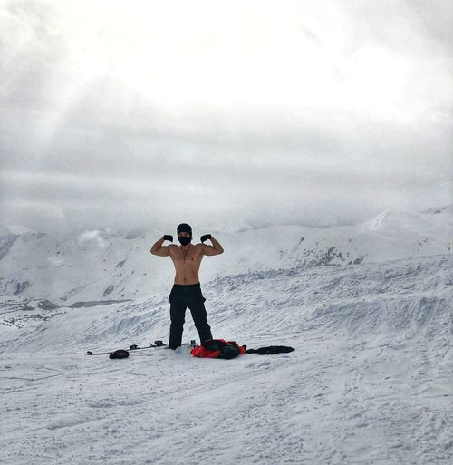 Portrait of shirtless man flexing muscles while standing on snowcapped mountains against cloudy sky