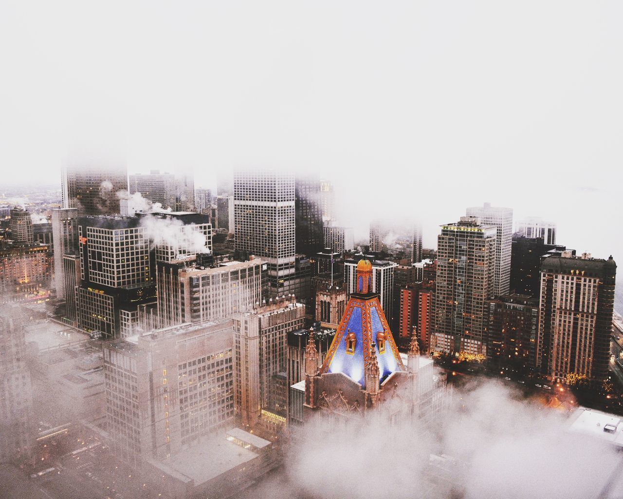 Clouds covering buildings in city