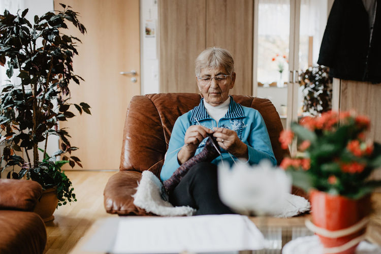 Sitting One Person Real People Adult Lifestyles Front View Indoors  Senior Adult Leisure Activity Furniture Holding Casual Clothing Plant Selective Focus Relaxation Home Interior Eyeglasses  Glasses Knitting Home Wool Stricken Wolle  Hobby