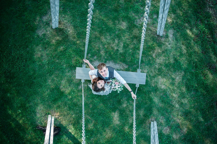 Bride and groom on swing at park