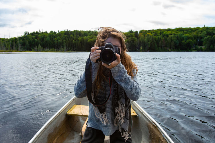 Woman photographing by lake against sky