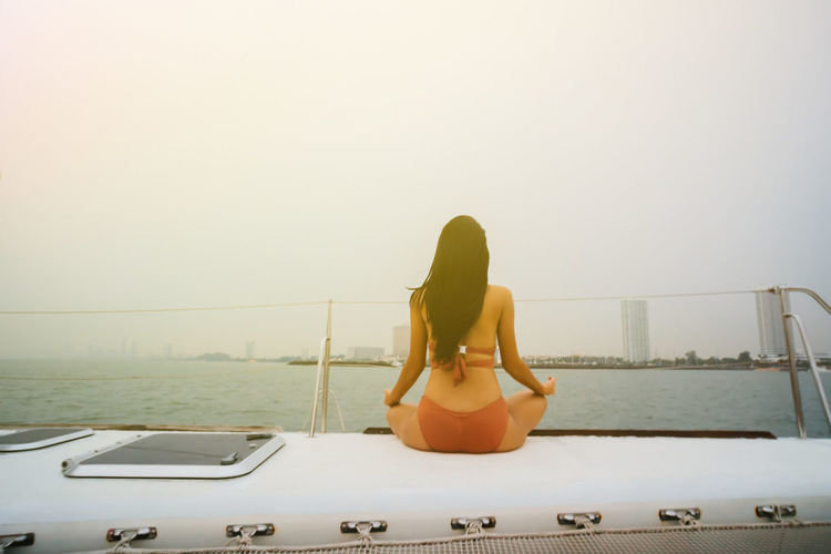 Rear view of woman in bikini by sea against clear sky