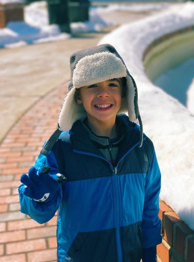 High angle portrait of happy boy in warm clothing standing at sidewalk