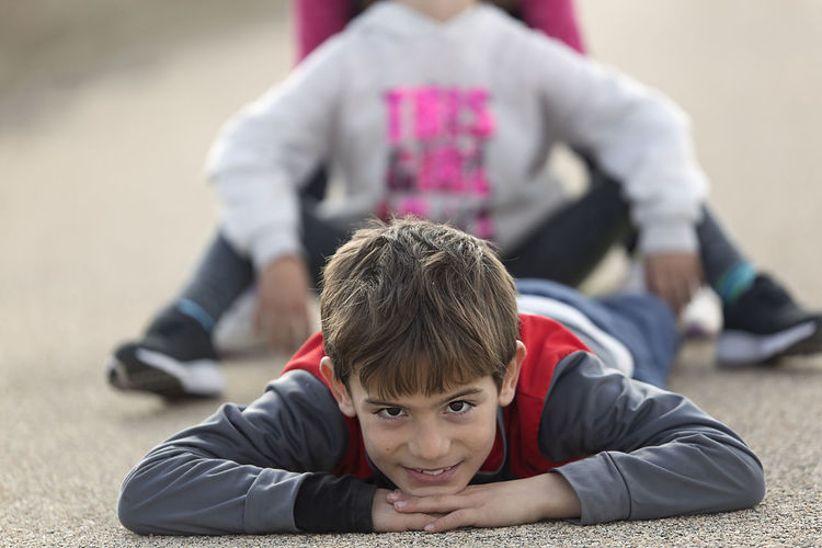 10 year old boy lying on the floor looking towards the camera. Horizontal shot with natural light Boy Boys Casual Clothing Childhood Day Elementary Age Focus On Foreground Leisure Activity Lifestyles One Boy One Person Outdoors Portrait Real People Sitting