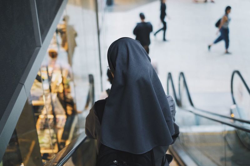 Rear View Of A Nun On Escalator