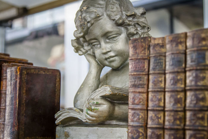 Angelic statue and old brown books on a bookshelf Books Knowledge Is Power Learning Printed Read Second Hand Angel Backgrounds Bookmarket Education Educational For Sale Hardcover Book Knowledge Literature Liturature Market Stall Novel Old Paperback Publication Second Hand Books Statue Used Vintage