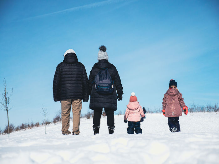 Rear view of people on snow against sky