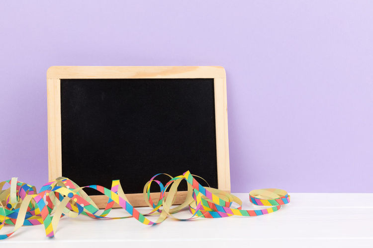 Close-up of blank slate and streamer against gray background