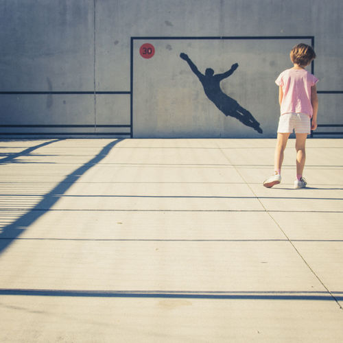Full length rear view of girl standing in basketball court