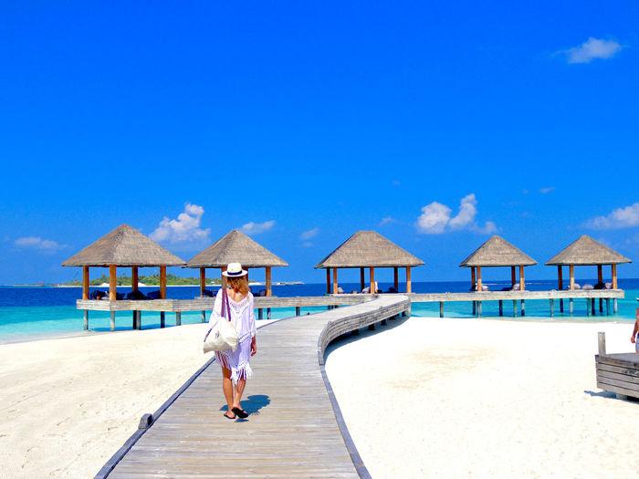 Woman on beach against blue sky