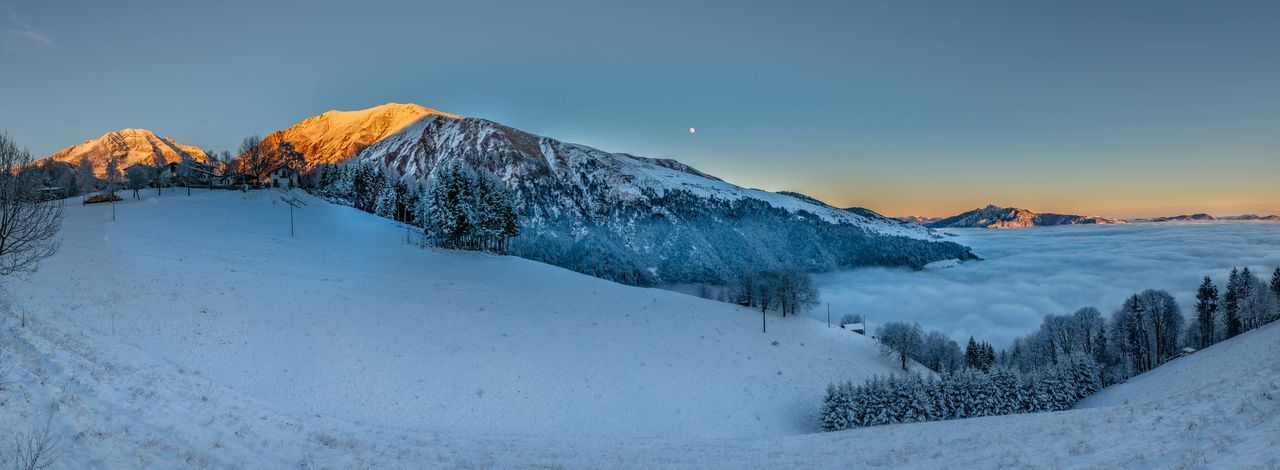 Snow covered land and mountains against sky during sunset