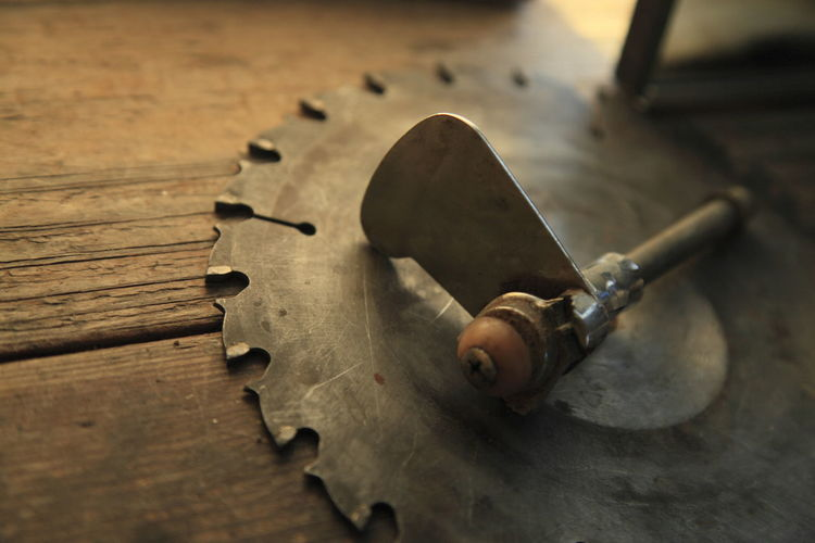 High Angle View Of Tool On Blade At Wooden Table