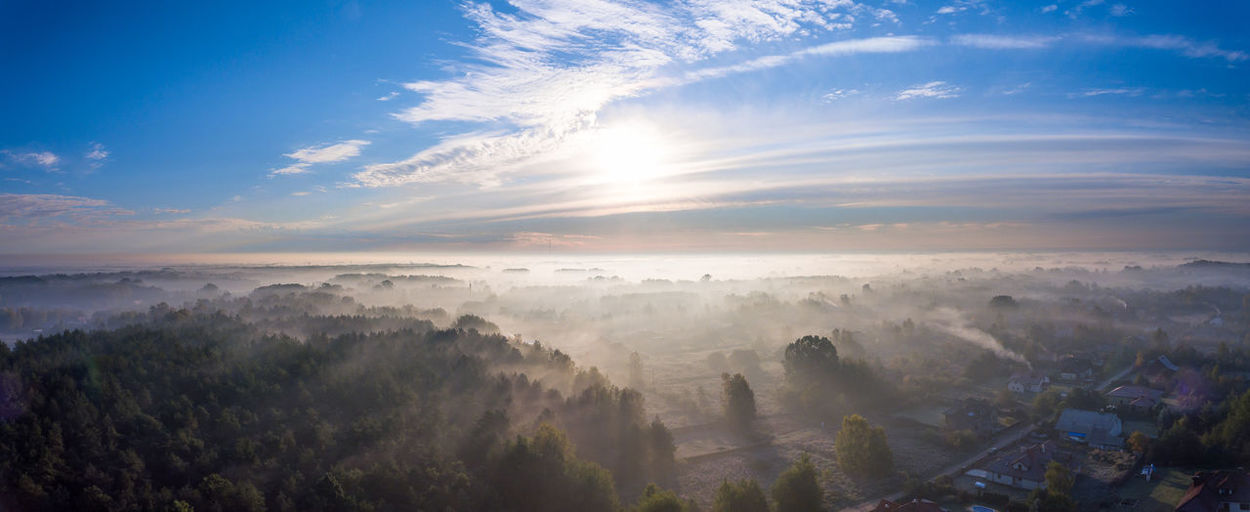 Rising sun on deep blue sky over a small village covered in mist. View from a drone. Beauty In Nature Cloud - Sky Day Flying High Fog Landscape Mountain Nature No People Outdoors Scenics Sky Sunlight Tranquil Scene Tranquility Tree