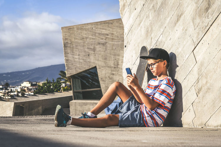 Full length of boy using phone while sitting outside building on sunny day