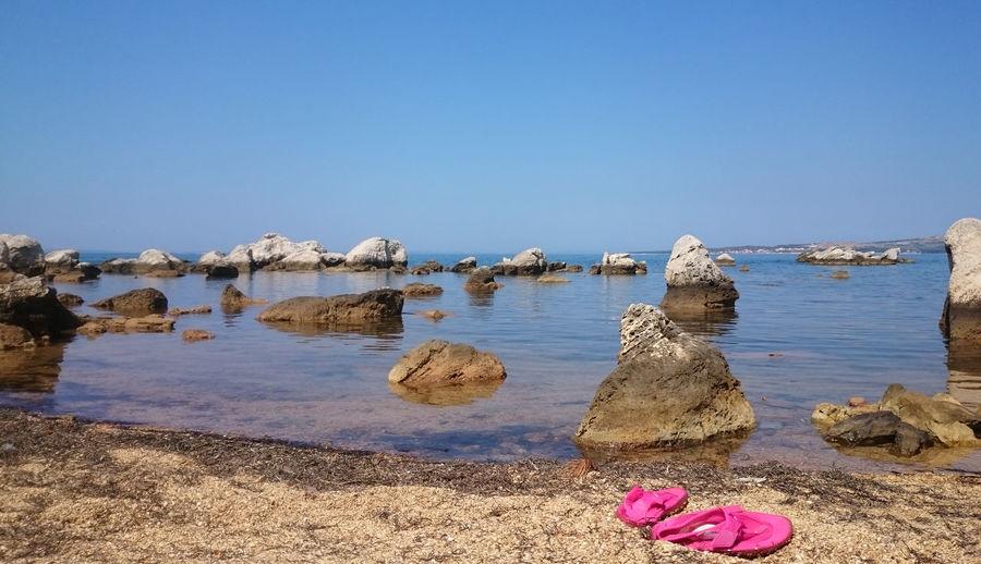 Calm sea against clear blue sky